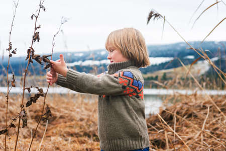 45 years old: Outdoor portrait of a cute little boy of 4-5 years old, playing by the lake on a cold day Stock Photo