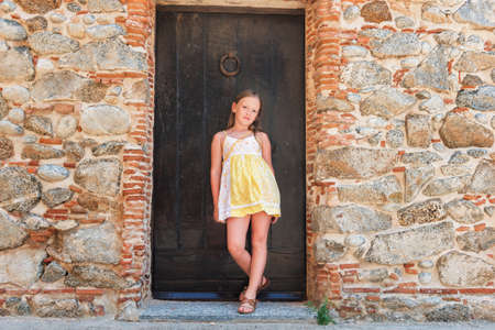 Outdoor fashion portrait of a cute little girl wearing yellow dress