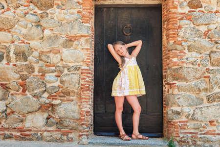 Retrato de moda al aire libre de una niña linda con un vestido amarillo