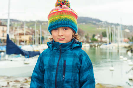 45 years old: Outdoor close up portrait of a cute little boy of 4-5 years old, wearing colorful hat and waterproof blue coat
