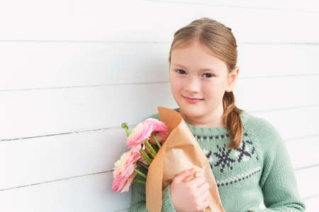 pretty preteen: Portrait of adorable little girl of 8-9 years old, wearing warm green pullover, holding spring pink flowers, standing against white wooden background, mothers day concept Stock Photo
