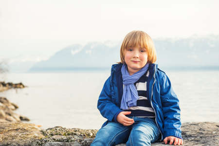 45 years old: Outdoor portrait of adorable little boy of 4-5 years old, resting by the lake, wearing warm blue jacket and scarf