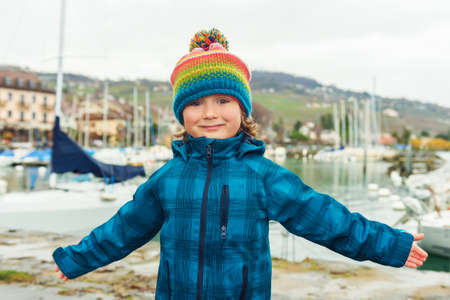 45 years old: Outdoor close up portrait of a cute little boy of 4-5 years old, wearing colorful hat and waterproof blue coat, arms wide open Stock Photo