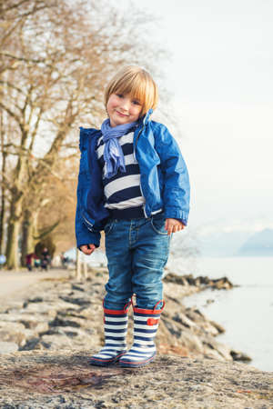 45 years old: Outdoor portrait of adorable little blond boy of 4-5 years old, having fun by the lake on a nice sunny spring day, wearing warm blue jacket, scarf, denim jeans and stripes rain boots