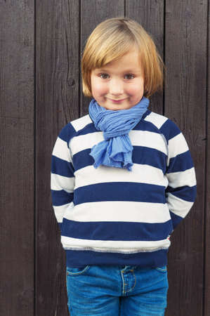 45 years old: Outdoor fashion portrait of adorable little boy of 4-5 years old, wearing stripes blue and white sweatshirt and scarf, standing against dark brown wooden background Stock Photo
