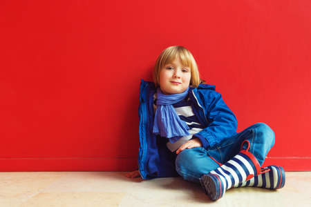 45 years old: Fashion portrait of adorable little boy of 4-5 years old, wearing blue jacket, scarf and stripes rain boots, sitting on the floor against bright red wall