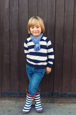 45 years old: Vertical fashion portrait of adorable little boy of 4-5 years old, wearing stripes blue and white sweatshirt, scarf, denim jeans and rain boots, standing against dark brown wooden background