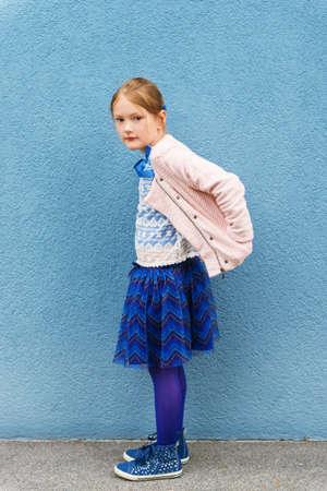 tights: Outdoor portrait of a cute little fashion girl, wearing pink jacket and blue skirt