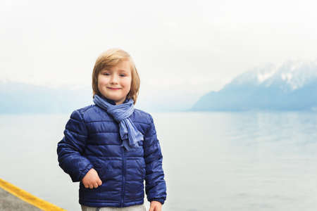 45 years old: Outdoor portrait of adorable little blond boy of 4-5 years old, wearing blue jacket and scarf, standing by the lake on a cloudy day