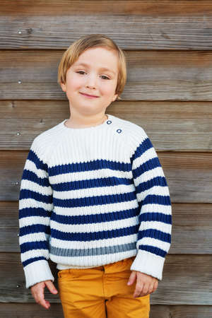 45 years old: Fashion vertical portrait of adorable little boy of 4-5 years old wearing warm white pullover with blue stripes and yellow trousers, standing against wooden background