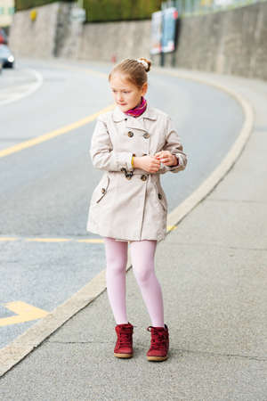 tights: Outdoor portrait of a cute little girl, wearing beige coat and red shoes Stock Photo