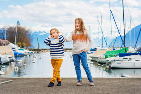 pullovers: Two adorable kids playing by the lake in early spring, wearing pullovers and colorful trousers