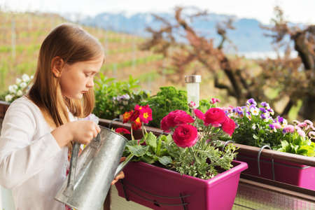 Adorable little girl watering flowers on the balcony Stock Photo