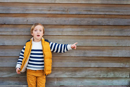 45 years old: Fashion little boy of 4-5 years old, wearing yellow vest, trousers and white pullover with blue stripes, standing against wooden background