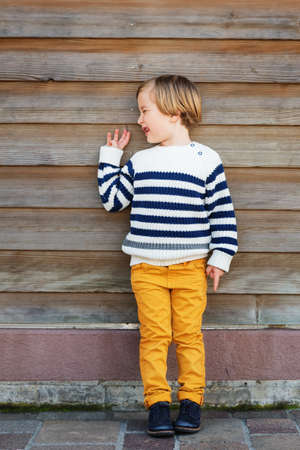 45 years old: Fashion little boy of 4-5 years old, wearing yellow trousers and white pullover with blue stripes, standing against wooden background