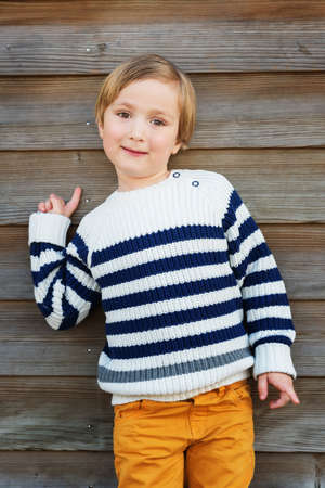 45 years old: Fashion vertical portrait of adorable little boy of 4-5 years old wearing warm white pullover with blue stripes and yellow trousers Stock Photo