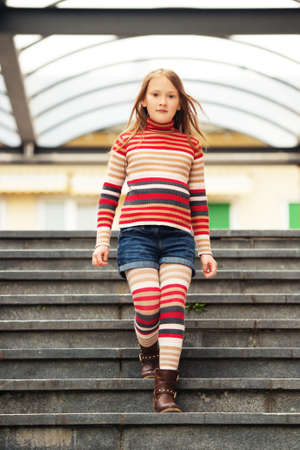 tights: Fashion portrait of a cute little girl in a city, wearing brown boots, denim shorts, stripes rollnecck pullover and tights