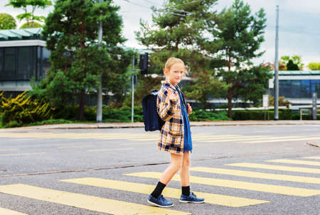 cross street with care: Pretty little schoolgirl with blue backpack crossing the road alone Stock Photo