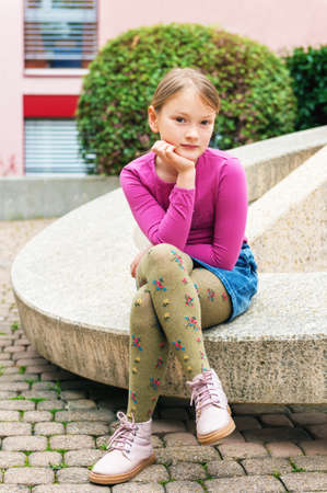 denim skirt: Fashion portrait of a cute little girl in a city, wearing pink shoes, t-shirt, denim skirt and green tights