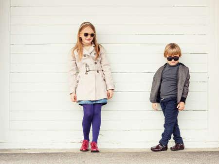 Fashion kids outdoors, wearing jackets and sunglasses