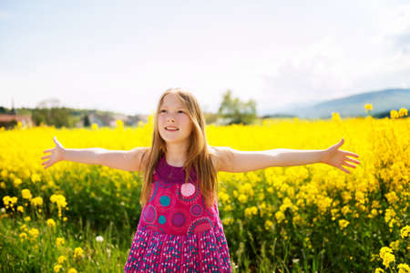 arms wide open: Outdoor portrait of a cute little girl playing with flowers in a countryside, arms wide open Stock Photo