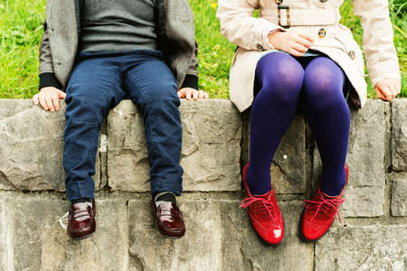 young girl feet: Two pairs of kids feet wearing fashion shoes, little boy wearing blue trousers and brown moccasins, schoolgirl in trench coat, purple tights and red brogues Stock Photo