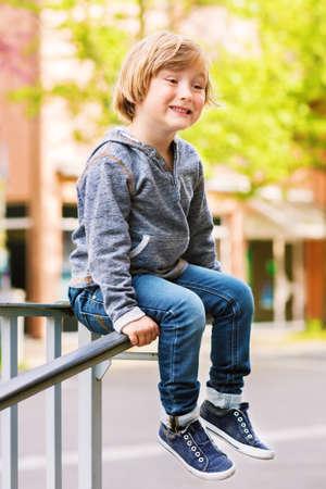 sudadera: Retrato de adorable ni�o peque�o que llevaba camiseta gris, pantalones vaqueros y zapatos de mezclilla Foto de archivo