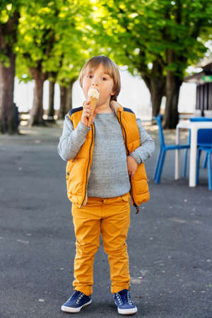 45 years old: Outdoor vertical portrait of adorable little boy of 4-5 years old, wearing blue pullover, yellow trousers and vest, eating ice cream in the park Stock Photo