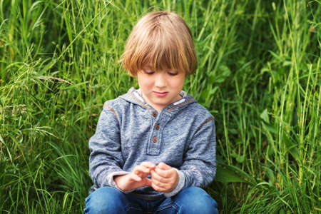 45 years old: Candid portrait of adorable little boy of 4-5 years old, wearing blue hoody, playing alone outdoors