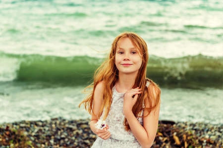 Pretty little girl with long red hair playing by the lake on a very windy day. Toned image Stock Photo