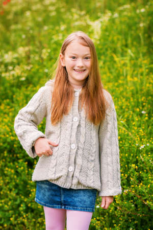 knitted jacket: Outdoor portrait of adorable little girl of 8-9 years old, wearing beige knitted jacket, posing in green field Stock Photo