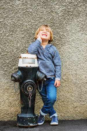 45 years old: Vertical portrait of adorable little boy of 4-5 years old, having fun outdoors, playing with black hydrant