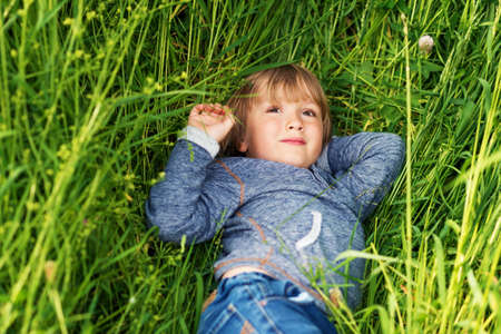 45 years old: Candid portrait of adorable little boy of 4-5 years old, wearing blue hoody, playing alone outdoors, laying on grass