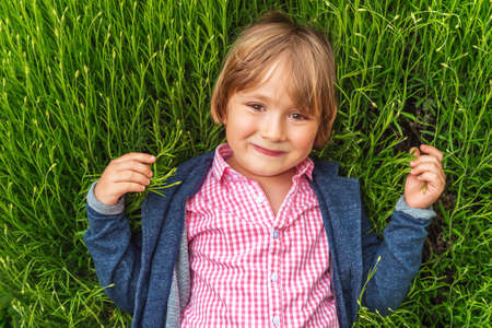45 years old: Candid portrait of adorable little boy of 4-5 years old, wearing pink shirt and blue jacket, playing alone outdoors, laying on grass