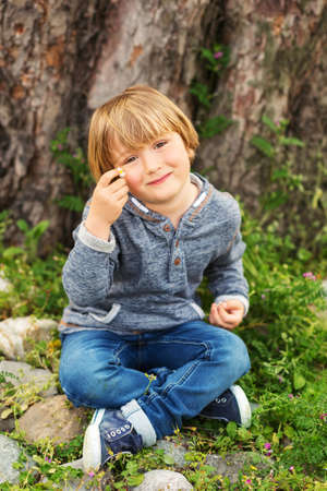 45 years old: Vertical portrait of adorable little boy of 4-5 years old, wearing blue hoody, playing alone outdoors