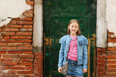denim skirt: Outdoor portrait of fashion little girl of 7-8 years old, wearing denim skirt and jacket, standing against old facade. Young tourist in Italy