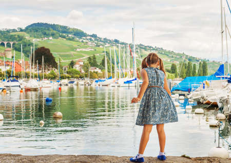 Fashion portrait of a cute little girl playing by the lake, wearing blue dress and mary jane shoes