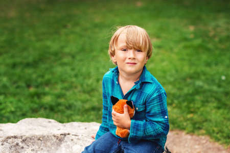 Outdoor portrait of adorable little boy of 4 years old playing in the park with a fox toy on a nice day, wearing emerald shirt