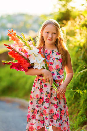 8 years old: Golden hour portrait of a cute little girl of 8 years old, holding colorful gladiolas flowers, vertical image Stock Photo