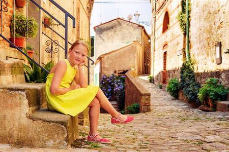 Lief klein meisje van 8 jaar oud, zittend op de trap in kleine oude Italiaanse stad in Toscane, Italië. Leuk preteen dragen groene jurk en rode schoenen