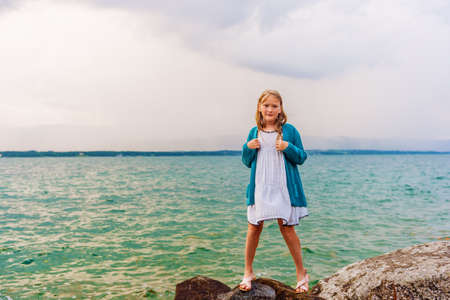 knitted jacket: Adorable little girl of 8-9 years old playing by the lake, wearing sandals, dress and blue knitted jacket Stock Photo
