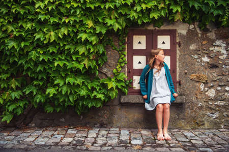 ivy wall: Outdoor fashion portrait of a cute little girl against ivy wall