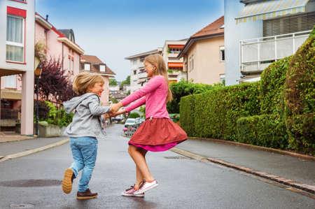 Adorable kids having fun outdoors, dancing on the street