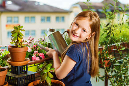 Adorable little girl watering plants on the balcony on a nice sunny day Archivio Fotografico