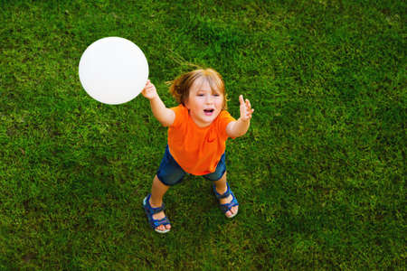 one child: Happy little boy of 4-5 years old playing with white balloon outdoors, top view