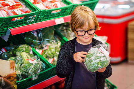 produce departments: Little boy choosing vegetables in a food store