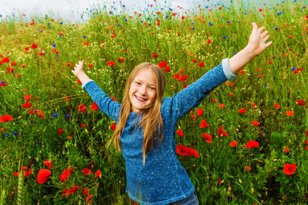 arms wide open: Outdoor portrait of adorable little blond girl of 8-9 years old in poppy field, arms wide open