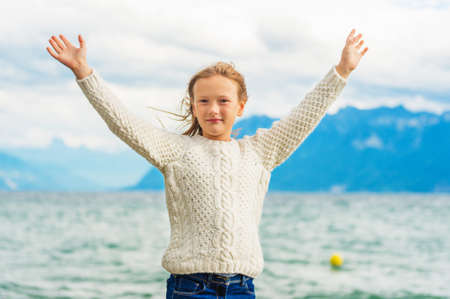 Cute little girl of 8 years old playing by the lake on a very windy day, wearing warm white knitted pullover, arms wide open Stock Photo