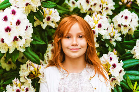 Close up outdoor portrait of adorable little girl of 8-9 years old . Red hair sweet young girl of 7-8 years old. Stock Photo