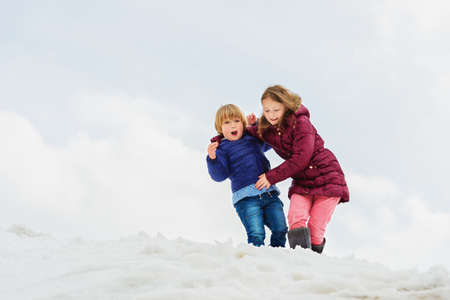 Winter portrait of two funny kids playing outdoors in mountains, wearing warm jackets